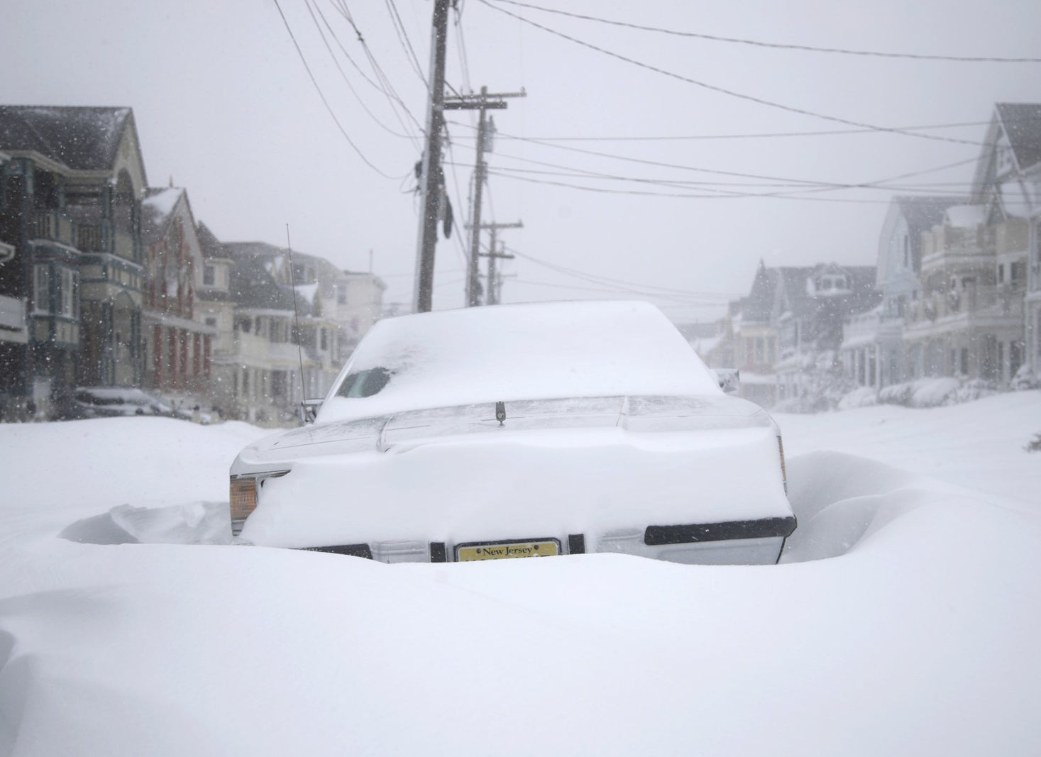 A parked vehicle is surrounded by snowdrifts along the Jersey Shore in Ocean Grove, New Jersey.
