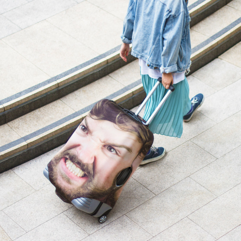 Person pulling suitcase with a personalized image of their scowling face on it