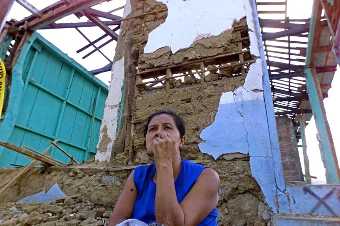 A woman sits before her earthquake-destroyed house in Armenia, El Salvador.