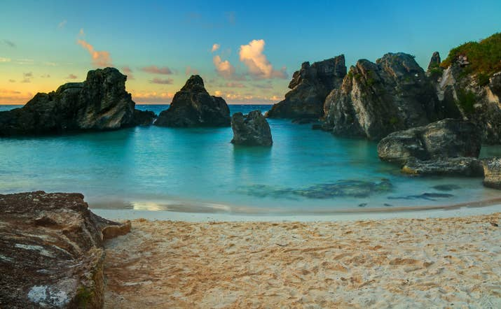 The tiny island of Bermuda floats in the Sargasso Sea, right off the coast of the Carolinas. The island is known for its colonial towns lined with pastel-colored houses, hidden coves covered in pink sand, and pleasant year-round weather perfect for golfing, swimming, or sun-bathing. Bermuda is also influenced by a mixture of British, West Indian, and Portuguese cultures, which is evident in the island's eclectic cuisine.