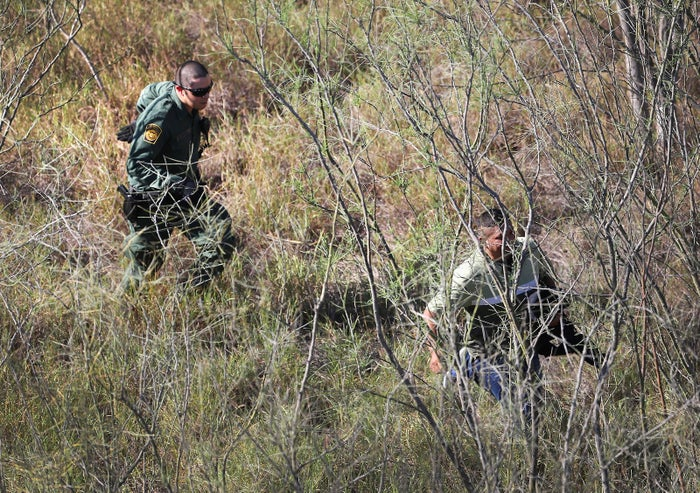A US Border Patrol agent chases an undocumented immigrant in thick brush near the US–Mexico border on Jan. 3, 2017, near Mission, Texas.