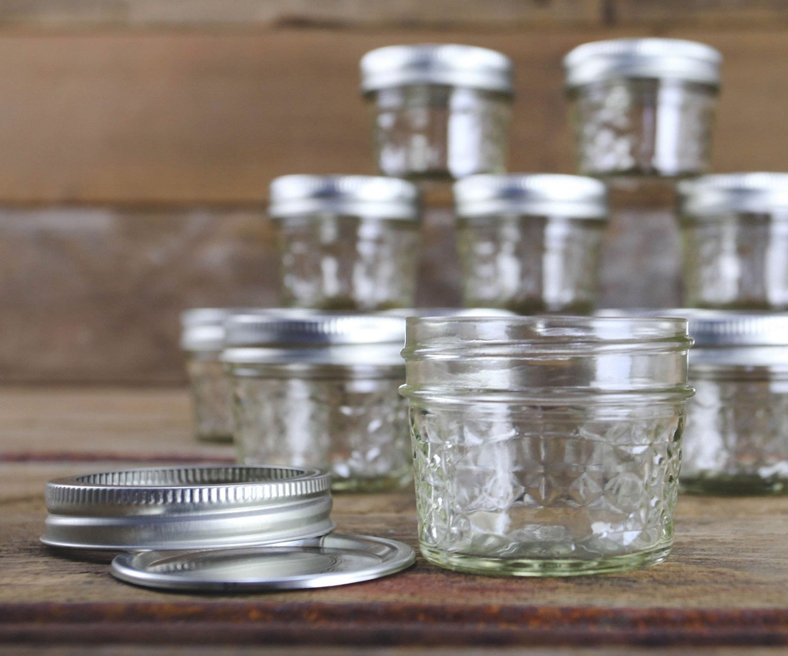 A 12-count of short glass jars with steel lids perfect for canning or preserving.