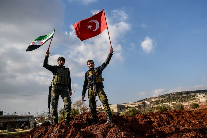 Turkish-backed Syrian rebel fighters hold Turkish national flag (right) and the Syrian independence flag (left) at a checkpoint in the Syrian town of Azaz on a road leading to Afrin, on Feb. 1.