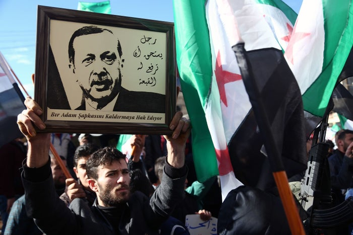 """A Syrian man raises a framed picture of Turkish President Recep Tayyip Erdogan next to a caption reading in Arabic and Turkish """"a man worthy of raising a hat for,"""" during a demonstration in the rebel-held town of Azaz in northern Syria."""