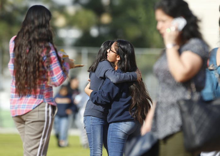 Students hug as people pick up students after a shooting at the Salvador B. Castro Middle School near downtown Los Angeles.