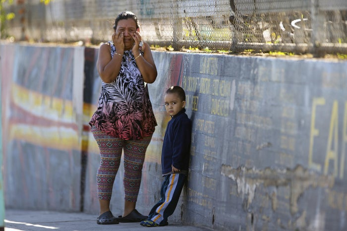 A mother and her child wait for news of her son at Belmont High School in Los Angeles.