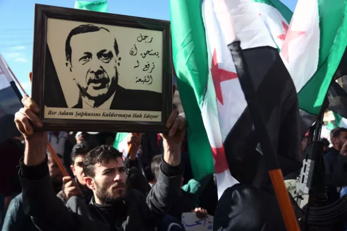 """A Syrian man raises a framed picture of Turkish President Recep Tayyip Erdogan next to a caption reading in Arabic and Turkish """"a man worthy of raising a hat for"""", during a demonstration in the rebel-held town of Azaz in northern Syria."""