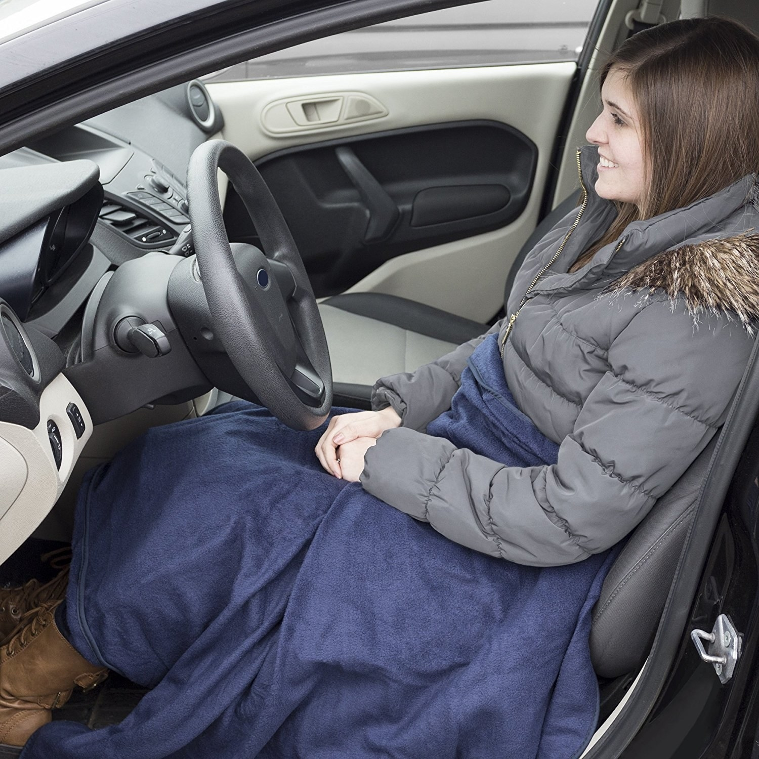 A photo of a person in their car wearing the electric fleece blanket.