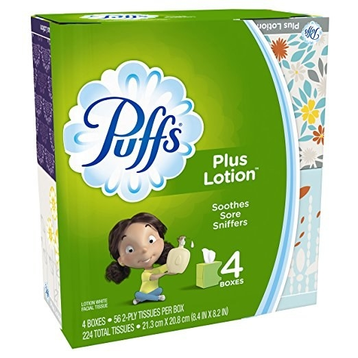 A green and blue tissue box that says the Puffs brand name on the top with a cartoon of a little girl holding a lotion bottle over a green box of tissues on the label.