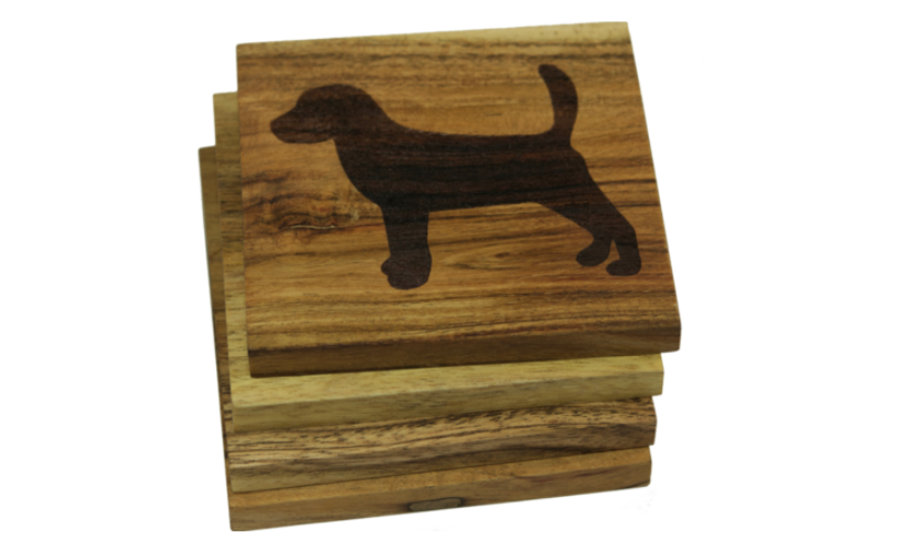 A set of handmade wooden coasters with engraved dog designs.
