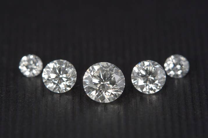 Generally, round brilliant-cut stones have the most sparkle because of the way they're cut. So unless your S.O. is hell bent on getting an emerald cut or something, go with round. The more sparkle the stone has, the less you'll notice any inclusions (flaws) or yellowish color.