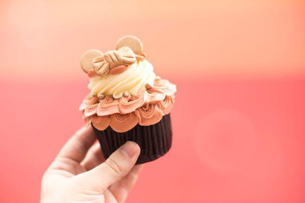 This super pretty vanilla cupcake with hazelnut swirl, rose gold buttercream, fondant ears, edible glitter, and chocolate pearls.