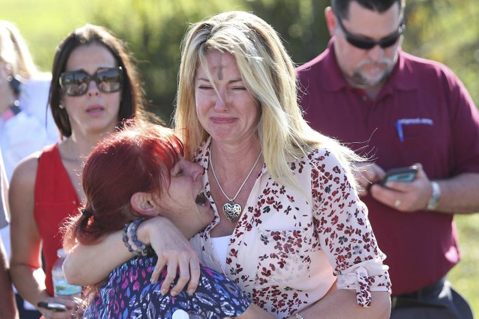 Parents wait for news after a reports of a shooting at Marjory Stoneman Douglas High School in Parkland, Florida.