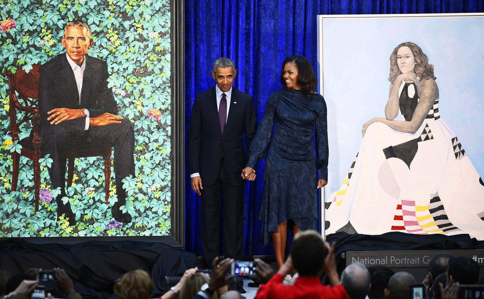 Former US president Barack Obama and former first lady Michelle Obama hold hands between their portraits during an unveiling ceremony at the Smithsonian's National Portrait Gallery in Washington, DC, on Feb. 12.