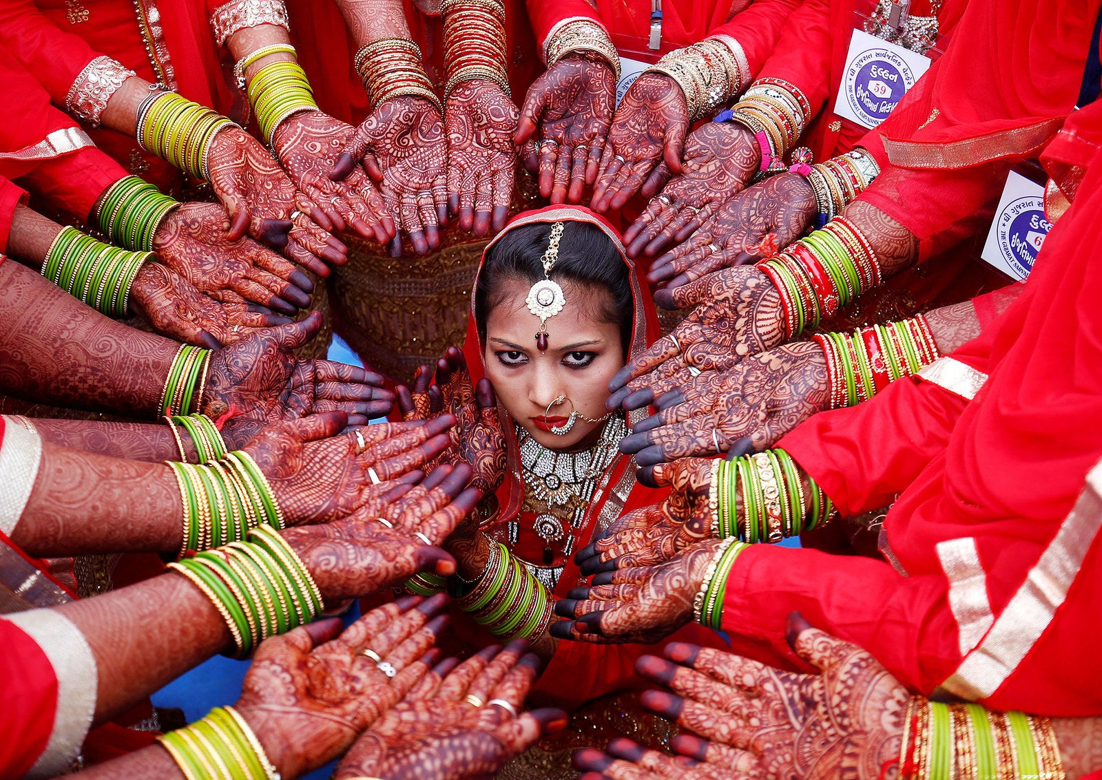 Brides display their hands decorated with henna during a mass marriage ceremony in which, according to its organizers, 70 Muslim couples took their wedding vows in Ahmedabad, India, on Feb. 11.