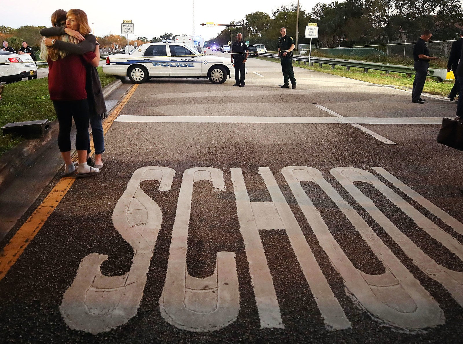 Kristi Gilroy (right) hugs a young woman at a police checkpoint near the Marjory Stoneman Douglas High School on Feb. 15, the day after 17 people were killed by a shooter at the Parkland, Florida, school. Police arrested the suspect after a short manhunt.