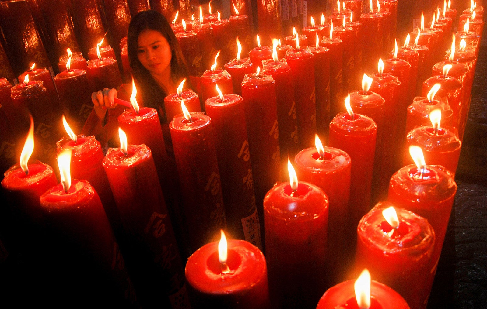 A woman lights a candle at a Chinese temple to mark the Lunar New Year in Bandung, West Java province, on Feb. 16.