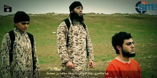 A frame from an ISIS video shows what appears to be a child at the execution of a prisoner.