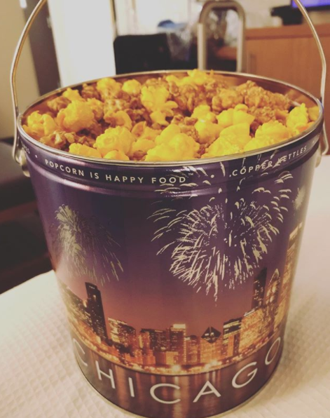 A giant tin of popcorn (usually from Garrett's) filled with Chicago mix  — AKA half cheddar and half caramel corn.