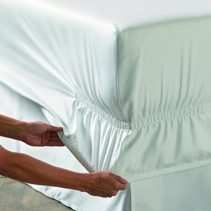 person pulling sheets down over corner, showing the deep pockets