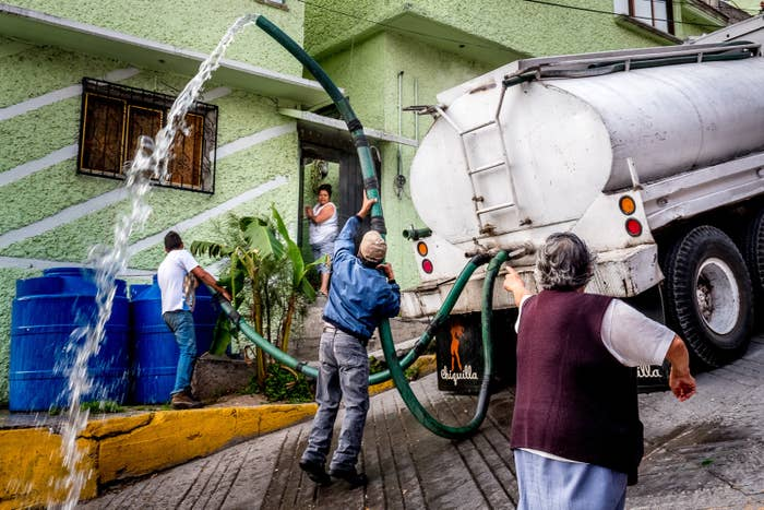 An elderly woman shouts at a water delivery truck for not visiting her home in over a week.