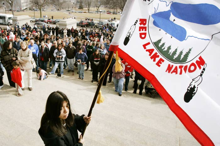 A flag-bearer and several hundred people hold a traditional Native American prayer service in St. Paul, Minnesota, in response to the shootings at Red Lake High School after a young man killed nine people at the school, including five students, before killing himself.
