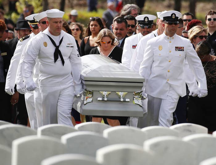Debra Hixon (center) follows the Naval Security Force Key West pallbearers as they carry the casket of her husband, Chris Hixon, who was the athletic director at Marjory Stoneman Douglas High School, for his burial at South Florida National Cemetery on Feb. 21, in Lake Worth, Florida.
