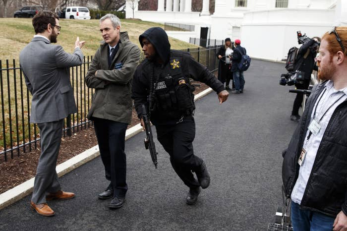A Secret Service officer rushes past reporters near the White House Friday.