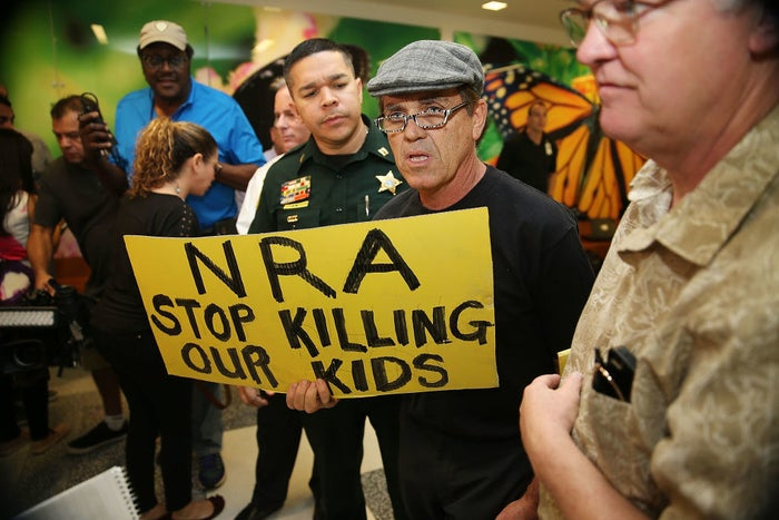 A protester holds a sign outside the courtroom where Nikolas Cruz, the accused Marjory Stoneman Douglas High School shooter, was having a bond hearing.
