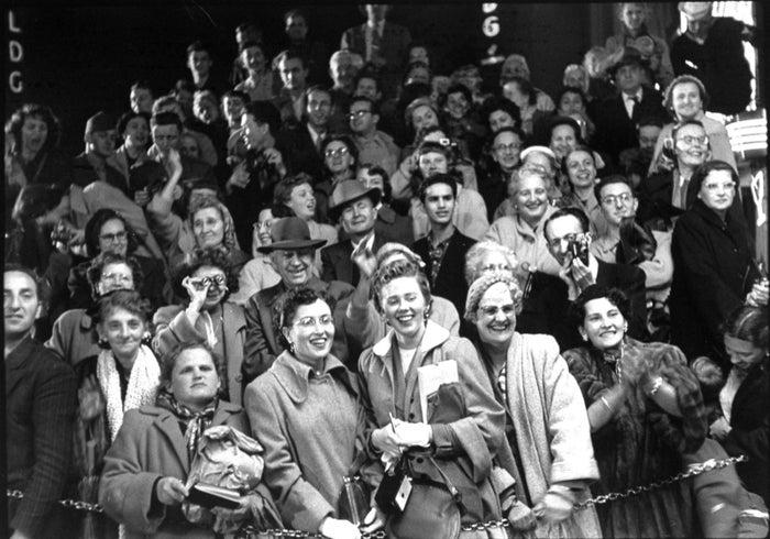 A crowd of fans watch as celebrities arrive for the 26th annual Academy Awards on March 25, 1954.