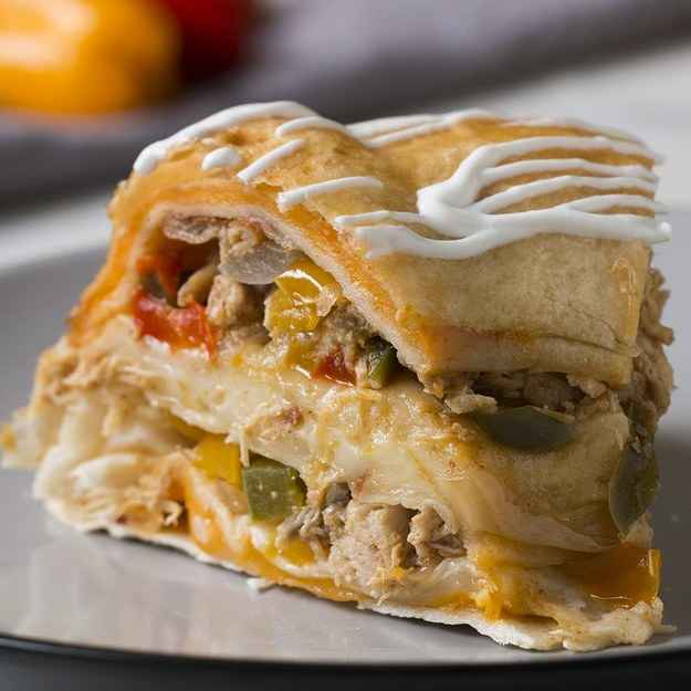 10 servingsINGREDIENTS6  flour tortilla2 tablespoons oil3  bell pepper, sliced1  large white onion, sliced2 teaspoons chili powder2 teaspoons cumin1 teaspoon garlic powder1 teaspoon salt910 g (2 lb) rotisserie chicken, shredded10 slices cheddar cheese, halved10 slices pepper jack cheese, halved sour cream, for serving guacamole, for servingPREPARATION1. Preheat the oven to 350˚F (180˚C). Grease a bundt pan with nonstick spray.2. Invert a 3-inch (8-cm) diameter bowl in the center of two tortillas. Use a knife to cut around the bowl and discard the centers.3. Invert a 2-inch (5-cm) diameter bowl in the center of two tortillas. Use a knife to cut around the bowl and discard the centers.4. Invert a 1½-inch (4-cm) diameter bowl in the center of one tortilla. Use a knife to cut around the bowl and discard the center.5. Heat the oil in a medium skillet over medium-high heat. Add the bell peppers and sauté until softened, about 5 minutes. Add the onion and toss to combine.6. Add the chili powder, cumin, garlic powder, and salt. Toss to combine.7. Add the chicken and cook until the onions are translucent and the chicken is warmed through.8. Place one of the tortillas with the 3-inch (8-cm) hole on the bottom of the greased bundt pan. Arrange a layer of cheddar cheese slices around the tortilla.9. Stack the second tortilla with a 3-inch (8-cm) hole over the cheese layer. Top the tortilla with half of the fajita mixture.10. Layer one of the tortillas with a 2-inch (5-cm) hole on top of the fajita layer. Top with a layer of Pepper Jack cheese.11. Layer the second tortilla with a 2-inch (5-cm) hole on top of the Pepper Jack layer.  Add the remaining fajita mixture.12. Layer the tortilla with a 1½-inch (4-cm) hole and top with the remaining cheddar and Pepper Jack.13. Layer the last tortilla on top of the last cheese layer.14. Cover the top of the bundt pan with a 12-inch (30 1/2-cm) round cake pan or aluminum foil and bake for 45 minutes.15. Let cool for at least 30 minutes.16. 