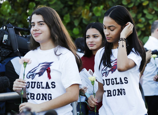 "Students wore t-shirts emblazoned with the words ""Douglas Strong"" and carried flowers as they made their way to school."