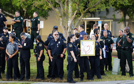 Some officers held signs of love and support as students walked to school.
