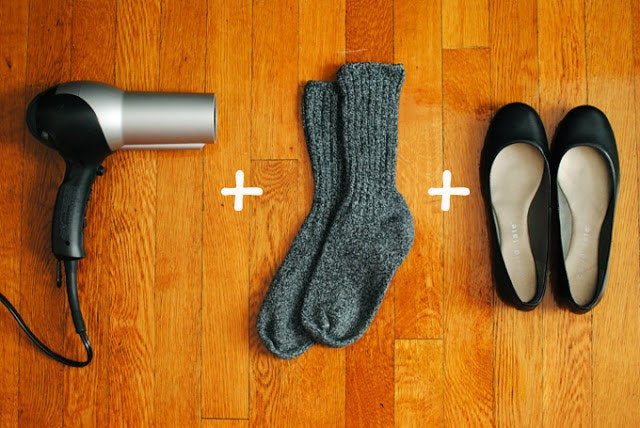 Put the shoes on while wearing the socks. Run the blow dryer over the tight part for a few seconds, then leave the shoes on until they're cool again. Take off the socks and try 'em out! From Coffee, Light and Sweet.