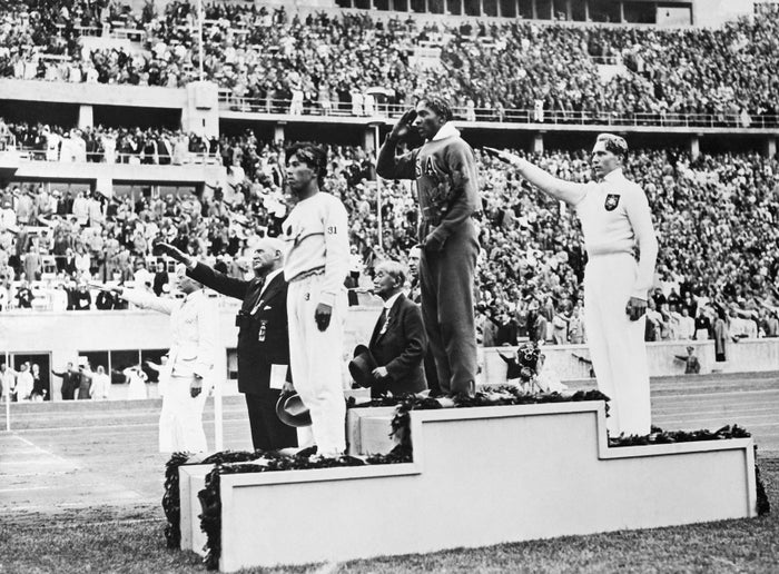 The medalists in the long jump competition salute from the victory stand at the 1936 Summer Olympics in Berlin on Aug. 8, 1936. From left, Japan's Naoto Tajima (bronze); American Jesse Owens (gold), who set an Olympic record in the event and offers an American-style salute with his hand to his forehead; and Germany's Luz Long (silver) giving a Nazi salute.