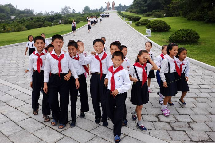 Schoolchildren make their way from the leaders' statues in central Hamhung.