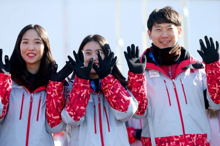Winter Olympics volunteers smile during the village's opening ceremony.