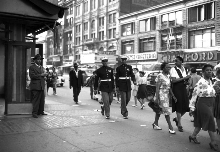 Two Marines walk down a street in Harlem during World War II in June 1943.