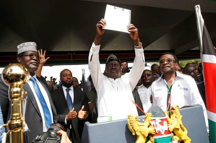 Kenyan opposition leader Raila Odinga (center) after taking a symbolic oath of office at the end of January, supported by Miguna Miguna (left).