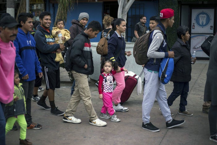 Mateo (in yellow) was carried by his father as they headed toward the US–Mexico border Nov. 12, 2017, in Tijuana.