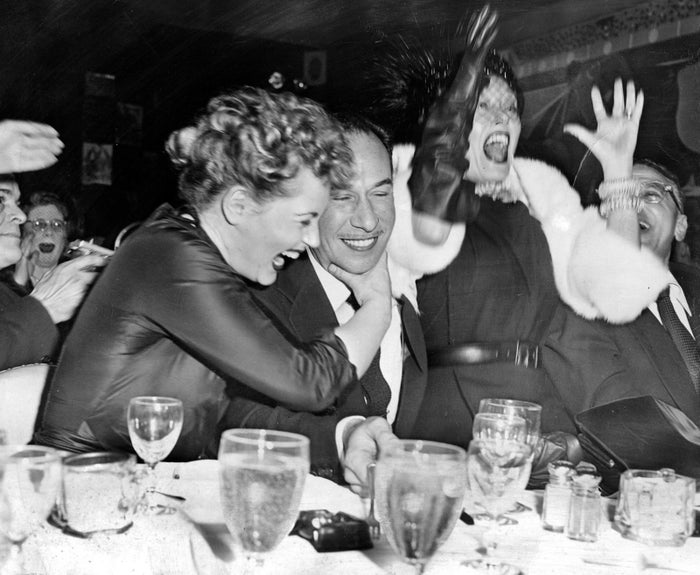 Judy Holliday (left) hugs José Ferrer (center) upon hearing the news that Ferrer's performance in Cyrano de Bergerac had earned him the Best Actor award in 1950. Holliday was named as the year's Best Actress. Gloria Swanson (right), who was in contention for the Best Actress award, jumps with joy over Ferrer's success.