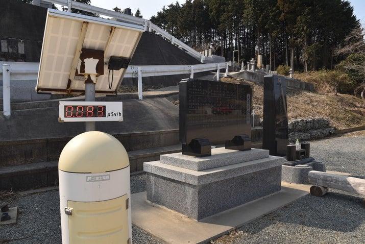 慰霊碑の横に設置されたモニタリングポスト(福島県南相馬市)