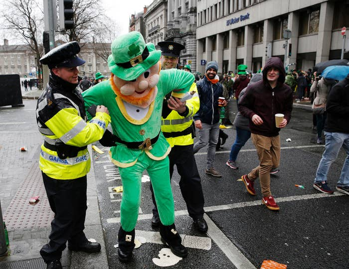 Police officers pretend to arrest a man dressed in a leprechaun outfit as he poses for a photograph along the St. Patrick's Day parade route in Dublin in 2017.