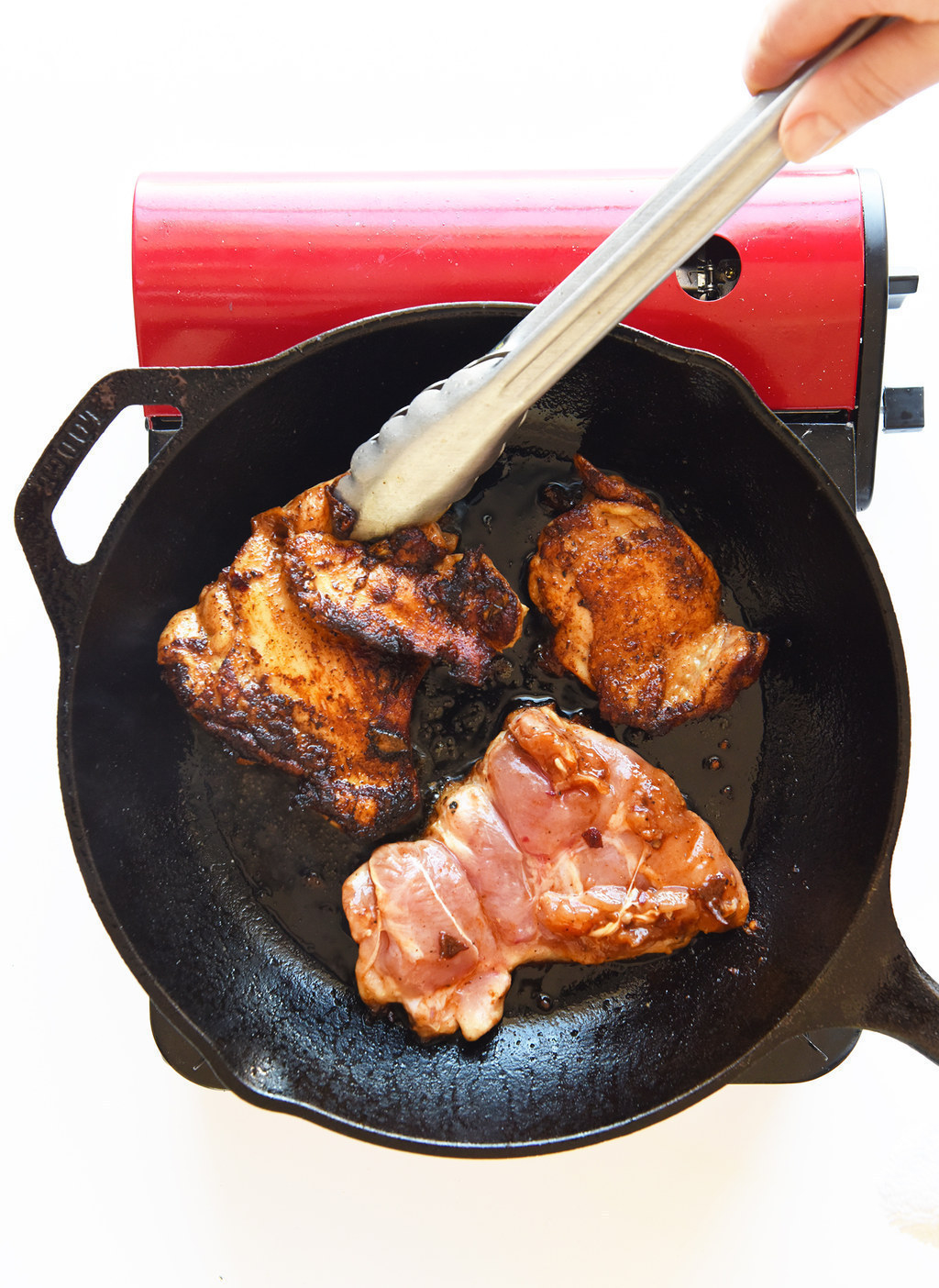 A cast iron pan with three caramelized chicken thighs