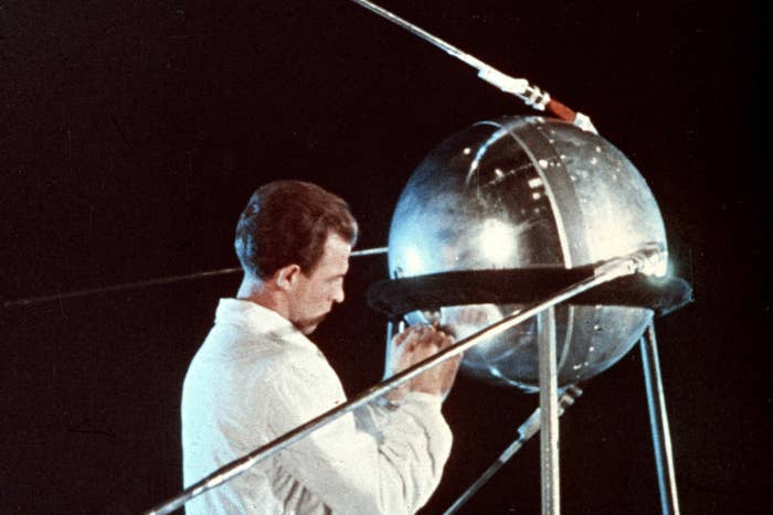 A Soviet technician works on the mechanics of the Sputnik 1 satellite in 1957.