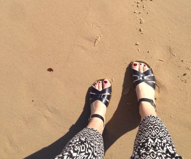 reader wearing the ankle-strap sandals with three criss-crossing straps on the toes in black on the beach