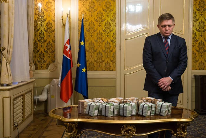 Robert Fico next to bundles of euro banknotes after offering a reward for information over the murders of Ján Kuciak and Martina Kušnírová.