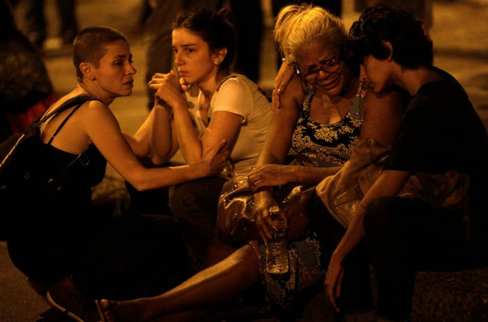 Women mourn the death of Marielle Franco, close to the scene of where she was shot.