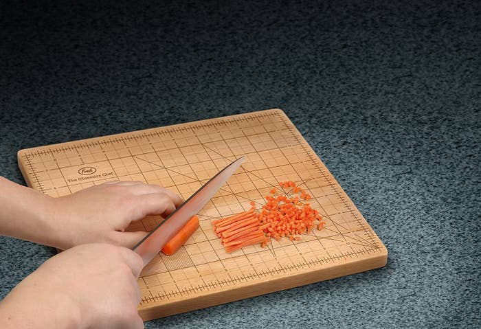 The cutting board with a grid of measurements to guide chopping, with someone julienning and small dicing a carrot on it