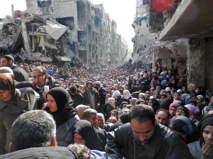 2014年1月31日にヤルムーク難民キャンプで国連機関が食料の配給を行った時に集まった人々